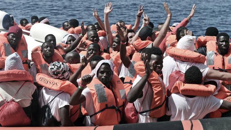"""Flüchtlinge von der """"Aquarius"""" winken, nachdem sie auf ein Boot der italienischen Küstenwache gebracht wurden."""
