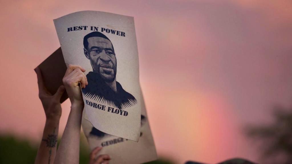 ARCHIV - Demonstranten halten während eines Protestes zettel mit dem Porträt von George Floyd, des in Minneapolis nach einem brutalen Polizeieinsatz gestorbenen Mannes afroamerikanischer Abstammung, in die Höhe. Foto: Christine T. Nguyen/Minnesota Public Radio/AP/dpa