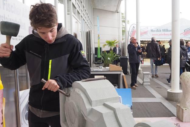 Liam Rothenbühler zeigt an einer Volute Steinmetzarbeiten.