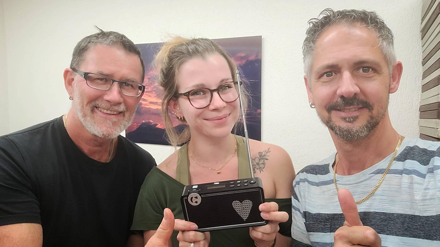 Siegerin Rebecca und ihre zwei Arbeitskollegen beim Radiohören.