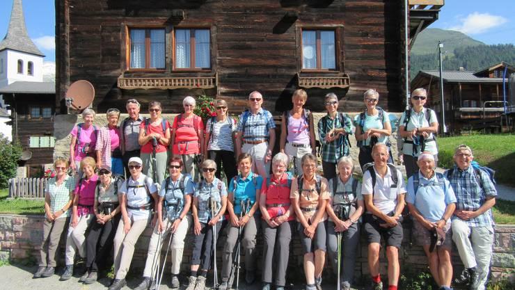 Gruppenfoto vor einem typischen geschmückten Walliserhaus