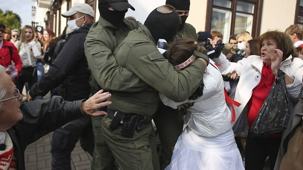 Polizisten nehmen eine Demonstrantin fest. Foto: -/Tut.by/AP/dpa