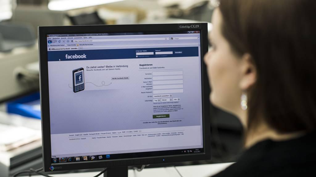Eine Frau loggt sich auf der Internetseite von Facebook ein.