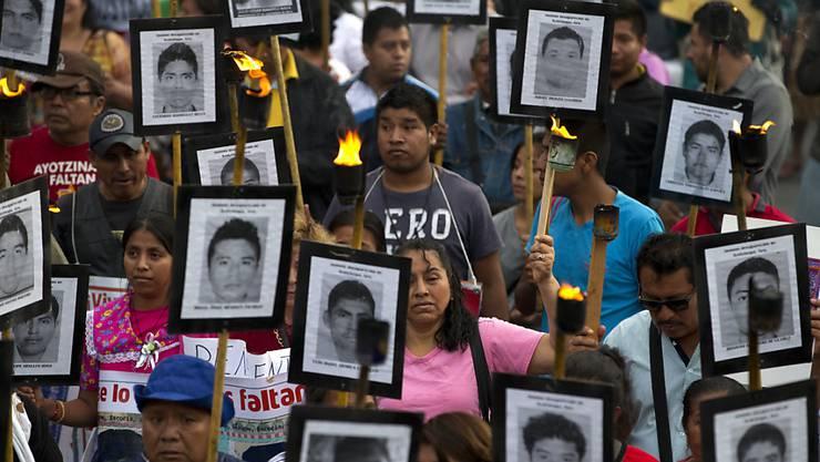 ARCHIV - Angehörige und Unterstützer tragen bei einem Protest-Marsch in Mexiko-Stadt im April 2016 Bilder der 43 vermissten Studenten. Foto: Rebecca Blackwell/AP/dpa