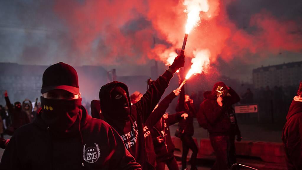 Anhänger der Gruppe «Men in Black» protestieren mit Bengalos gegen die Corona-Maßnahmen der Regierung auf der Straße in Kopenhagen. Foto: Martin Sylvest/Ritzau Scanpix/AP/dpa