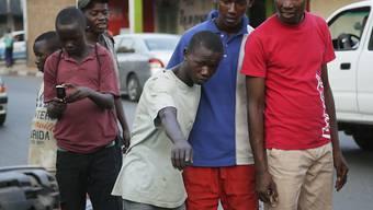 Passanten in Burundis Hauptstadt Bujumbura schauen sich den Schaden an, den eine Granate verursacht hat.