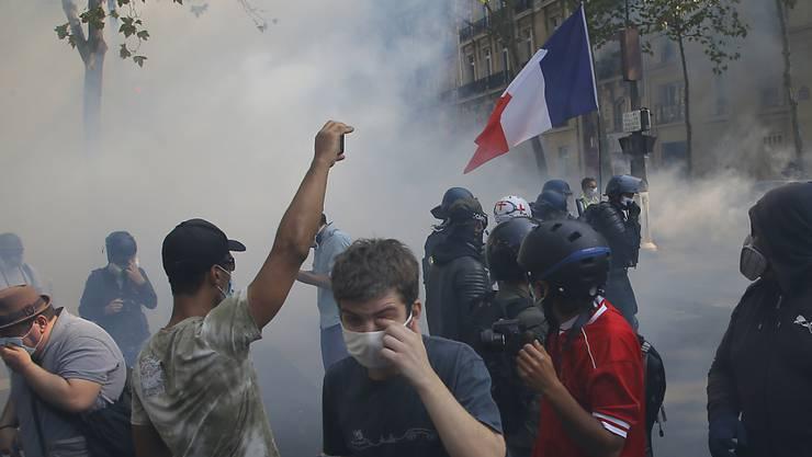 «Gelbwesten»-Demonstranten gehen in Paris vor Tränengas in Deckung. Foto: Michel Euler/AP/dpa