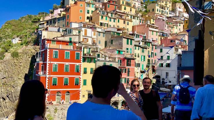 Jeder will ein Selfie vor dieser Kulisse: Touristen in Riomaggiore in der Cinque Terre, Italien.