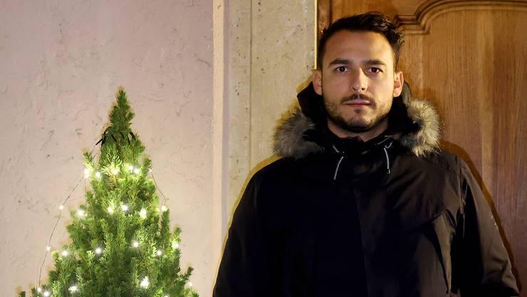 Sehid Sinani posiert weihnachtlich mit Tannenbaum.