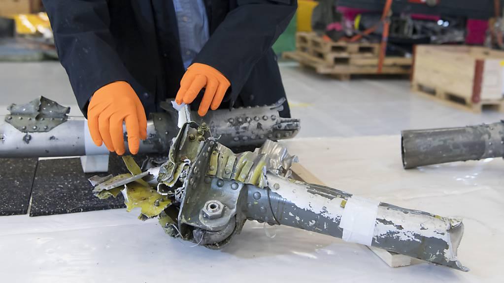 Ein Mitarbeiter der Sicherheitsuntersuchungsstelle (Sust) des Bundes schaut sich Wrackteile des in Graubünden 2018 abgestürzten Oldtimerfliegers Junkers Ju 52 an. (Archivbild)