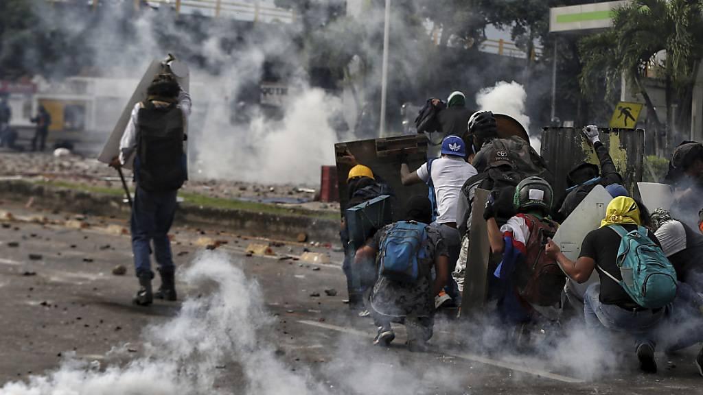 Demonstranten stoßen während eines nationalen Streiks gegen die Steuerreform mit der Polizei zusammen. Kolumbiens Präsident Duque hatte zuvor die von der Regierung vorgeschlagene Steuerreform zurückgezogen. Foto: Andres Gonzalez/AP/dpa