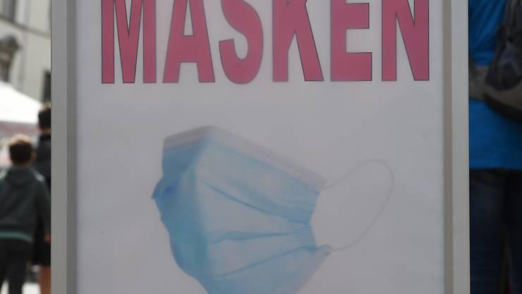 """ARCHIV - """"Masken"""" steht auf einem Schild in einem Geschäft in der Innenstadt von Stralsund. Die WHO empfiehlt das Tragen von Masken für Kinder ab zwölf Jahren. Foto: Stefan Sauer/dpa-Zentralbild/dpa"""