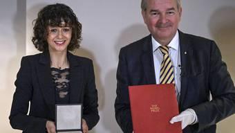 Die Mikrobiologin Emmanuelle Charpentier zeigt die Medaille zu ihrem Nobelpreis für Chemie, die sie am Montagabend von Schwedens Botschafter Per Thöresson (r) in Berlin überreicht bekommen hat. Die Verleihung am 10. Dezember in Stockholm findet dieses Jahr wegen der Corona-Pandemie nur online statt.