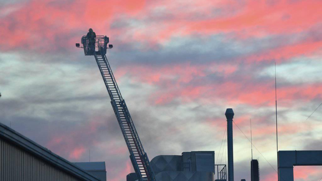Feuerwehrleute sind nach dem Brand auf dem Betriebsgelände von Rolls-Royce in Oberursel (Hessen) im Einsatz. Der Brand war nach Feuerwehrangaben in der alten Härterei des Betriebs nach Dacharbeiten ausgebrochen.