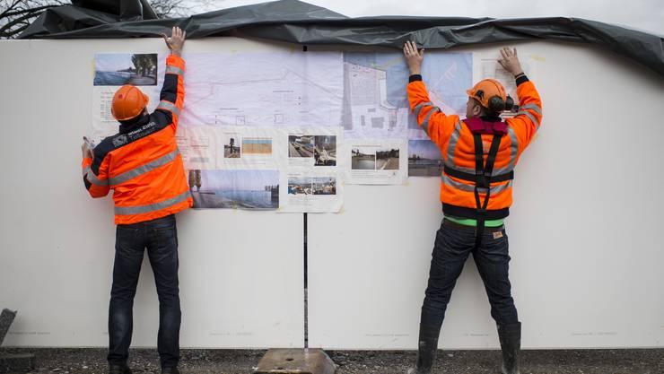"""Mitarbeiter enthüllen den Plan vom """"Cassiopeiasteg"""" am Seeuferweg in Wollishofen, aufgenommen am Montag, 2. März 2015 in Zürich."""