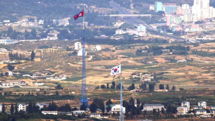 Die Flaggen von Nordkorea (hinten) und Südkorea (vorne) im Grenzgebiet der beiden Staaten. Foto: Seo Myung-Gon/YONHAP/AP/dpa