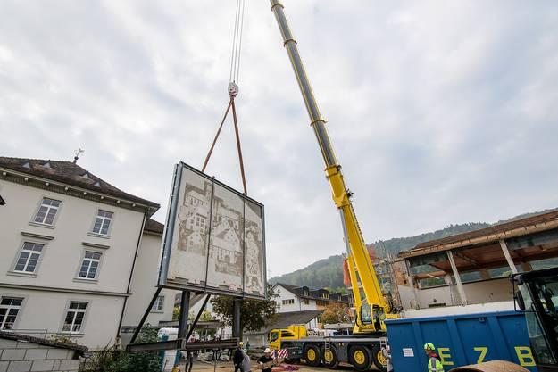 Während der Kran vor dem neuen Zuhause des Sgraffito in Position gebracht wird, muss es zwischen Turnhalle und neuem Heim zwischengelagert werden.