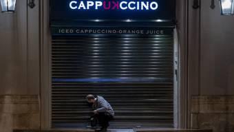 dpatopbilder - Ein Angestellter schließt ein Café vor der Sperrstunde in Barcelona. Foto: Emilio Morenatti/AP/dpa