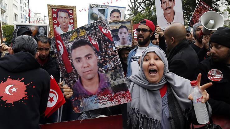 Gedenken an die Märtyrer: Demonstranten in Tunis zeigen Fotos von Angehörigen, die während gewaltsamen Auseinandersetzungen getötet wurden.