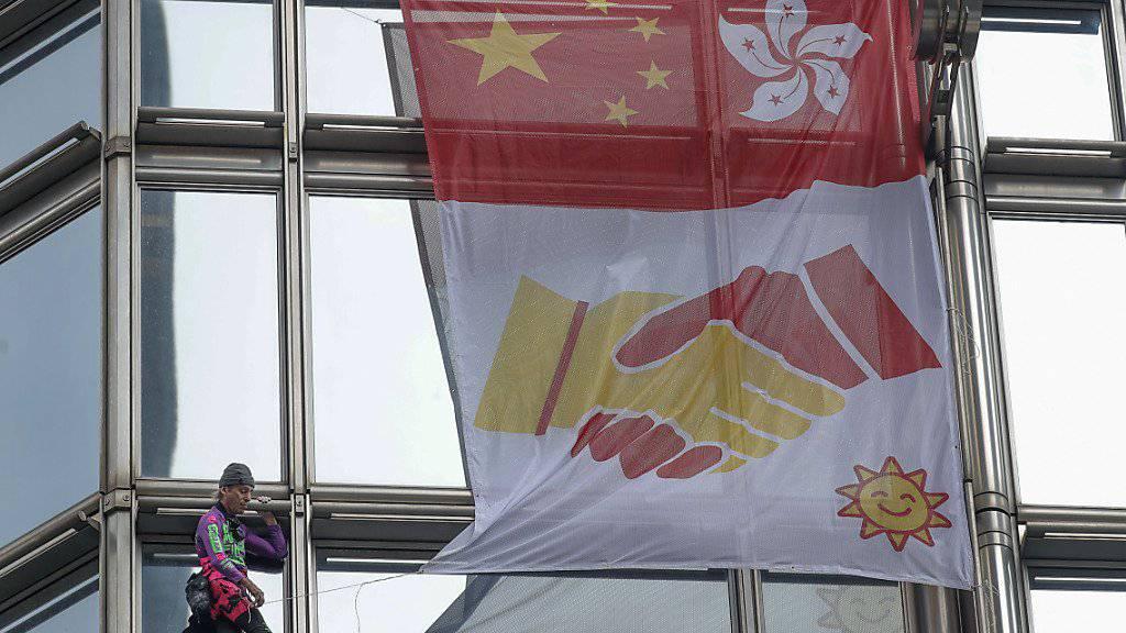 Der Extremkletterer Alain Robert rollte am Freitag in Hongkong an einem Wolkenkratzer ein «Friedensbanner» aus.