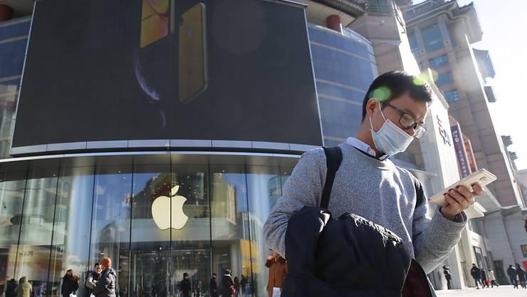 Apple stemmt sich gegen ein drohendes Verkaufsverbot in China: ein Mann in Hong Kong mit seinem Smartphone.