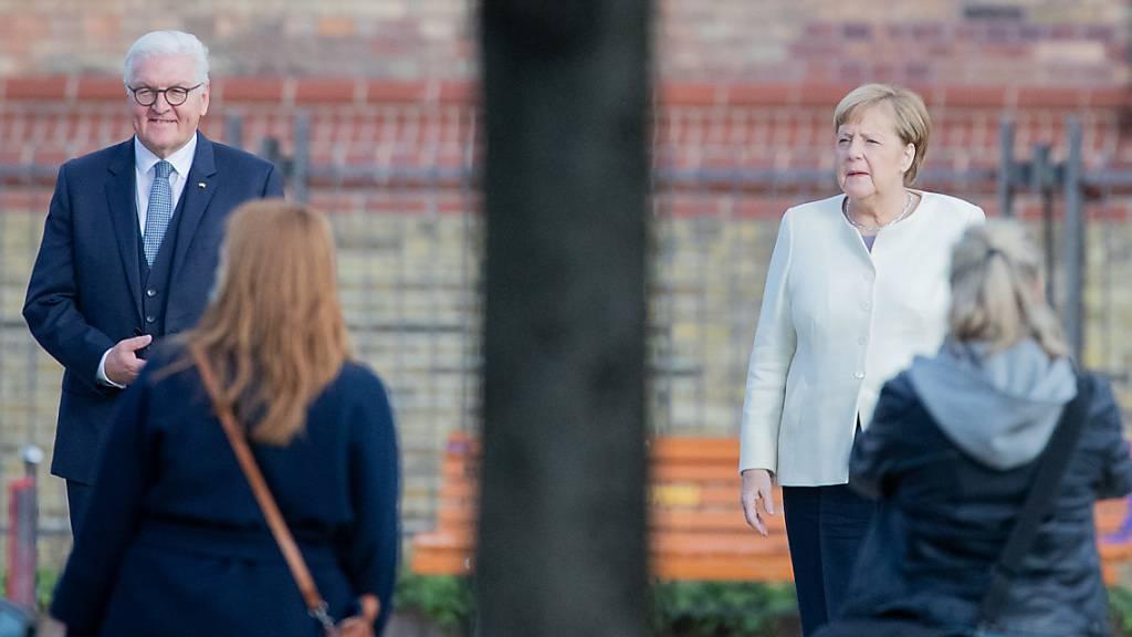 Bundespräsident Frank-Walter Steinmeier und Bundeskanzlerin Angela Merkel (CDU) stehen für ein Gruppenfoto vor einem ökumenischen Gottesdienst vor der Kirche St. Peter und Paul. Foto: Christoph Soeder/dpa