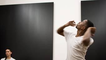 Vor schwarz lackiertem Aluminium versucht ein Performer (rechts), sich um sich selbst zu drehen, während seine Kollegin durch die Besucher hindurchstarrt.