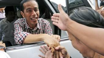 Indonesiens Präsident Joko Widodo - hier 2014 während des Wahlkampfs - scheint ein unkomplizierter Typ zu sein: Nachdem dieser Tage seine Limousine im Stau feststeckte, ging er halt zu Fuss weiter.