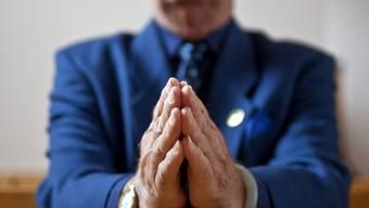 Ein Gottesdienstbesucher faltet die Hände zum Gebet (Symbolbild)