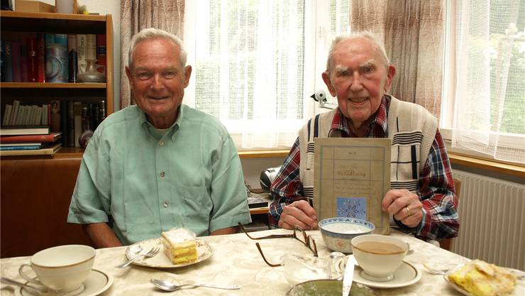 Thomas Gutermann (links) und Karl Frey mit dem Heft seiner ersten persönlichen Wetteraufzeichnungen von 1927, unterhalten sich bei ihren Treffen in alter Freundschaft über Erinnerungen, Wetter und Klimawandel. hub