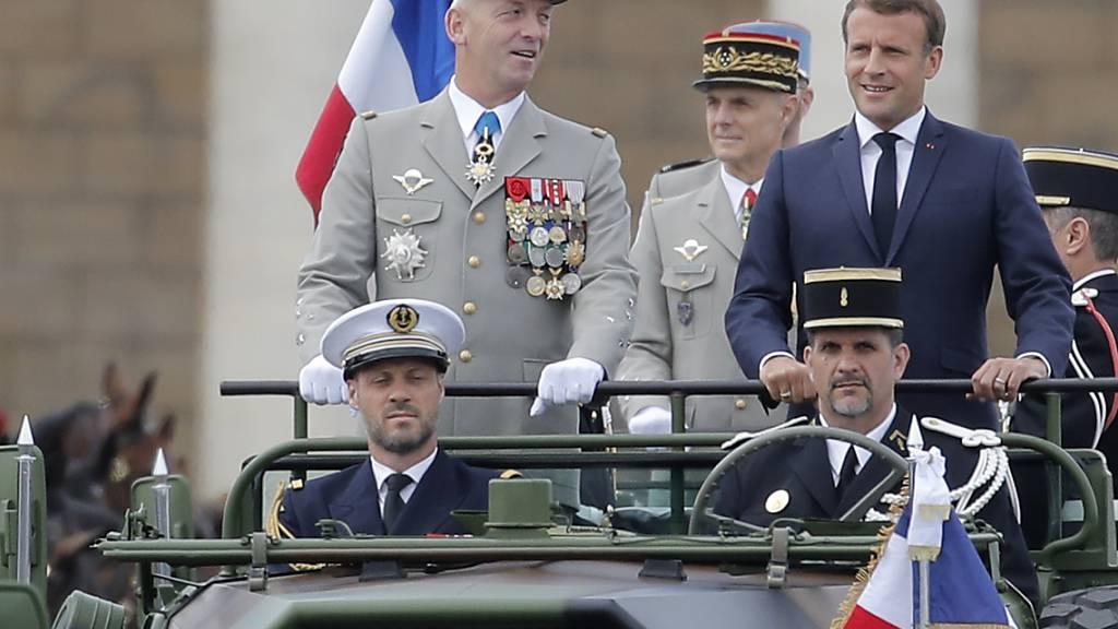Emmanuel Macron (r), Präsident von Frankreich, und der Generalstabschef der französischen Armeen, General Francois Lecointre stehen im Kommandowagen, während der Militärparade zum französischen Nationalfeiertag. Foto: Christophe Ena/AP/dpa