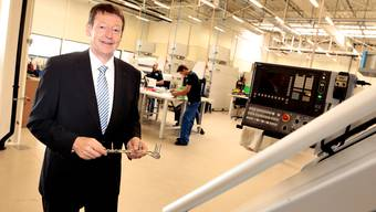 Thomas Wahl zeigt eine im Hightech-Neubau in Selzach produzierte Knochenplatte mit Schrauben.