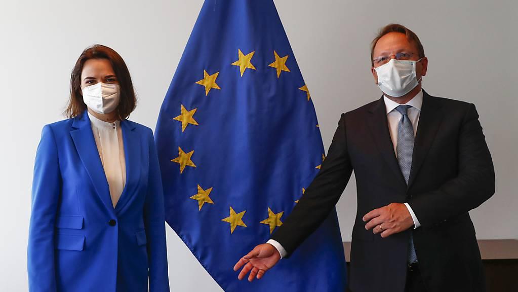 Swetlana Tichanowskaja, Oppositionsführerin aus Belarus, und Oliver Varhelyi, Erweiterungskommissar der EU, stehen zusammen vor einer Fahne der EU während eines Treffens der Aussenminister der EU im Gebäude des Europäischen Rates.