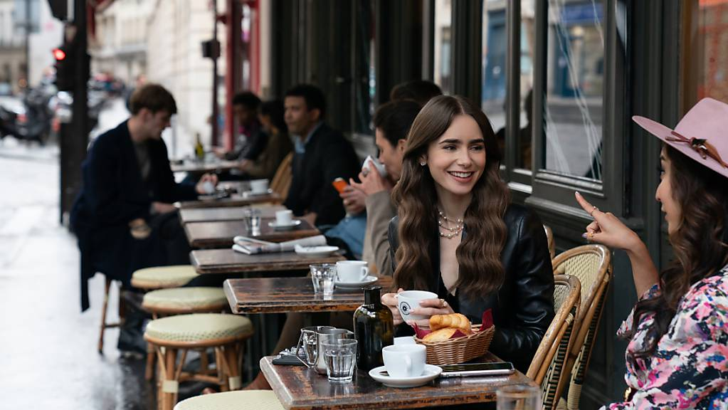 Emily (Lily Collins, Mitte) sitzt mit einer Freundin im Café – eine Filmszene aus der ersten Staffel der Netflix-Serie «Emily in Paris».