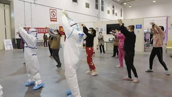 In einem temporären Spital in Wuhan macht medizinisches Personal mit Corona-Patienten Gymnastikübungen.