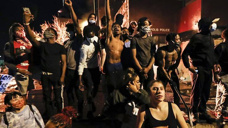 Demonstranten stehen vor einem brennenden Gebäude des 3. Bezirks der Polizei von Minneapolis während der Proteste nach dem Tod von George Floyd, der in Folge einer brutalen Festnahme durch einen Polizisten in Minneapolis starb. Ein weißer Polizist hatte bei der Festnahme lange auf dem Hals des Afroamerikaners gekniet, welcher mehrmals darauf aufmerksam machte, dass er nicht atmen könne. Foto: John Minchillo/AP/dpa