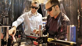 Die PSI-Forscher Loïc Le Guyader (links) und Souliman El Moussaoui justieren den Laser, mit dem die magnetische Probe erhitzt wird (Archiv)