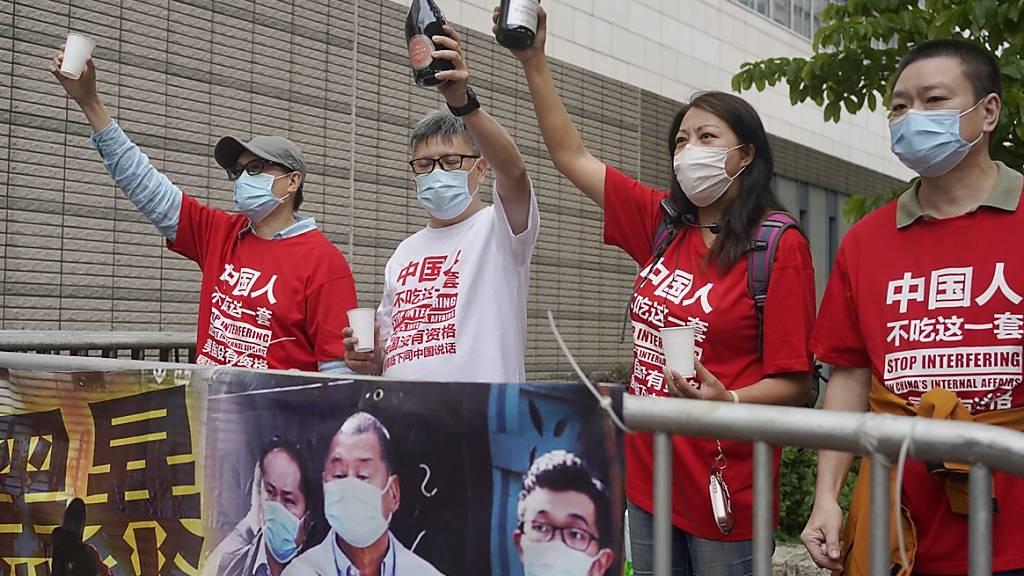 Pro-Chinesische Aktivisten feiern das Urteil mit Champagner. Ein Hongkonger Gericht verkündete das Strafmaß gegen neun bekannte demokratische Aktivisten und Politiker wegen illegaler Versammlung 2019. Foto: Vincent Yu/AP/dpa