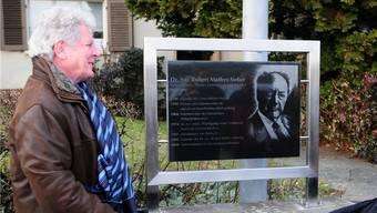 Gemeindepräsident Hans Kübli und Lisbeth Mathys enthüllen die Gedenktafel für Robert Mathys. hps