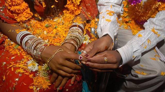Ein junges indisches Paar tauscht im Rahmen einer Massenhochzeit Ringe aus (Symbolbild)