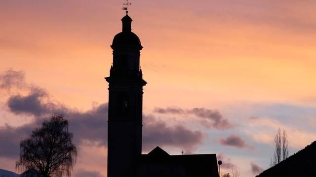 Morgenrot über einer Pfarrkirche im Kanton Graubünden (Symbolbild)