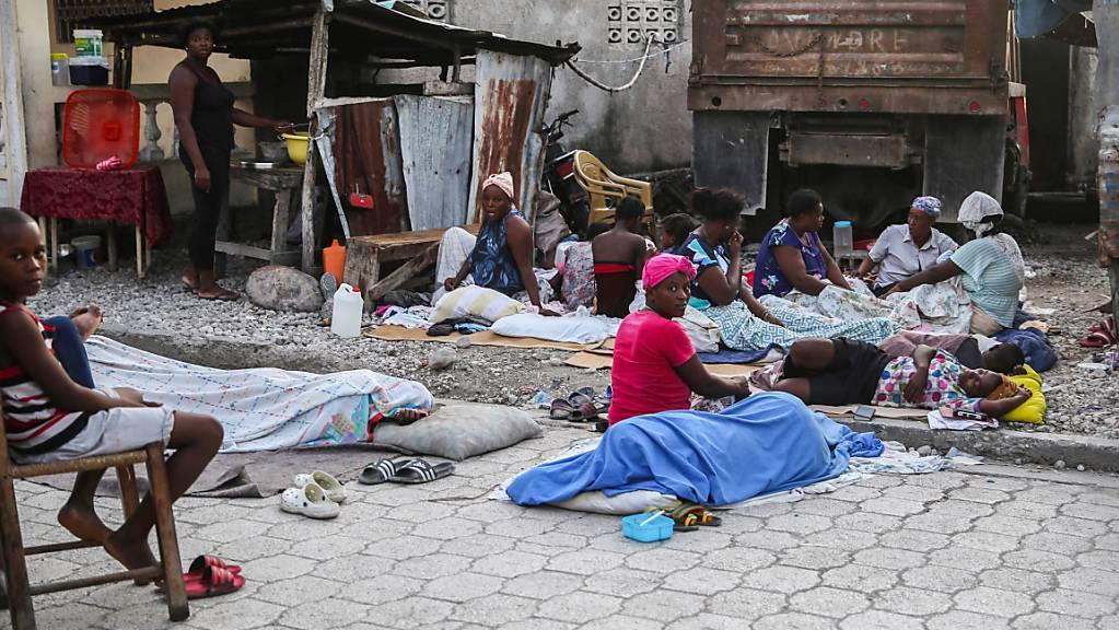 Einheimische, die die Nacht in Schlafsäcken im Freien verbracht haben, wachen am Tag nach einem Erdbeben auf. Das Erdbeben der Stärke 7,2 hat Haiti am 14.08.2021 erschüttert. Foto: Joseph Odelyn/AP/dpa