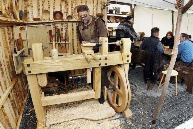 Ein Drechsler mit seiner selbstgebauten Maschine, daneben wird der Geselligkeit gefrönt.