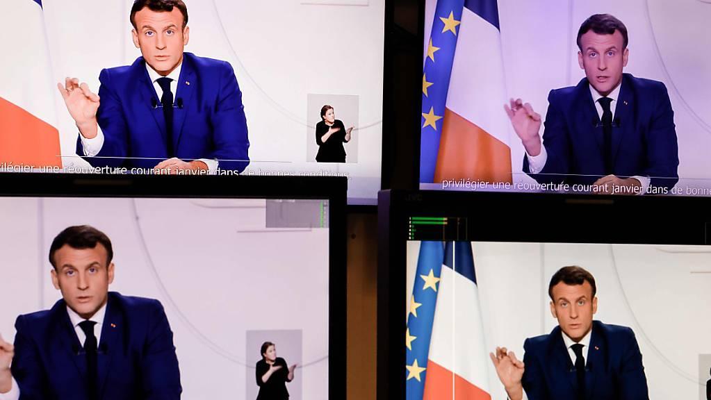 Die abfotografierten Bildschirme zeigen Emmanuel Macron, Präsident von Frankreich, der eine Fernsehansprache an die Nation zur aktuellen Corona-Lage hält. Angesichts einer verbesserten Corona-Lage hat Frankreichs Präsident Macron erste Lockerungen der strengen Beschränkungen im Land angekündigt. Foto: Thomas Coex/AFP/dpa - ACHTUNG: Nur zur redaktionellen Verwendung im Zusammenhang mit der aktuellen Berichterstattung und nur mit vollständiger Nennung des vorstehenden Credits