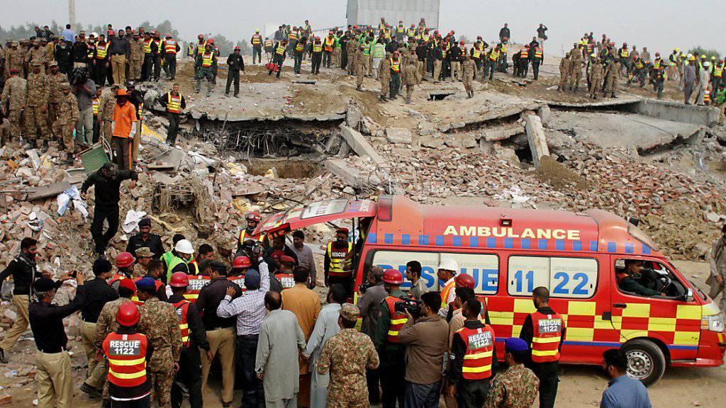 Pakistanische Soldaten, Rettungskräfte und Freiwillige suchen in den Trümmern der eingestürzten Fabrik nach Verschütteten.