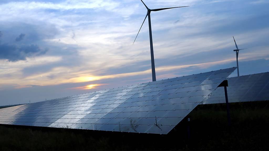 ARCHIV - Der mit Wolken überzogene Abendhimmel spiegelt sich auf den Solarzellen einer vor Windrädern stehenden Solarkraftanlage. Foto: Karl-Josef Hildenbrand/dpa