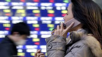 Eine Japanerin telefoniert vor einer elektronischen Börsenkursanzeige in Tokio (Archiv)
