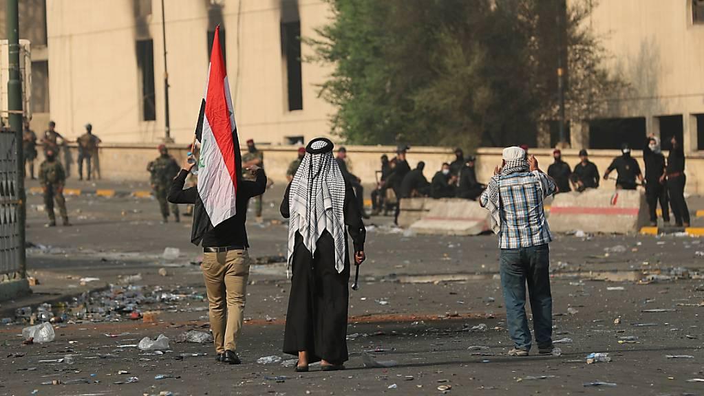 Frustration über Korruption und Stillstand: Irakische Sicherheitskräfte riegeln die Grüne Zone in Bagdad ab, während im Vordergrung Zivilisten demonstrieren.