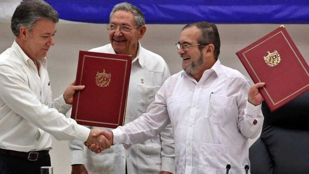 """Kolumbiens Präsident Juan Manuel Santos (links) und FARC-Chef Rodrigo Londono alias """"Timochenko"""" nach der Unterzeichnung des Waffenstillstands am Donnerstag in Havanna."""