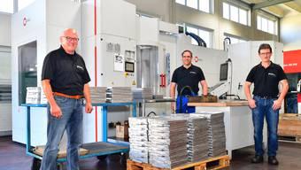 Inhaber Hansjörg Zingg (links), Daniel Marti (mitte) und Martin Bobst (rechts, beide Geschäftsleitung) vor dem 5-Achs-Bearbeitungscenter, in dem derzeit einzelne Teile für Coronavirus-Analysegeräte nach dem Giessen in der Giesserei nachbearbeitet werden.